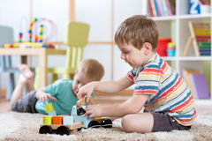 Children boys toddlers playing with toy car indoors. Two children boys play together educational toys in playroom stock photography