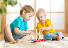 Children boys with toys in playroom Stock Photos