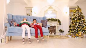 Children boys are upset and show discontent, sitting on blue sofa in festive decorated room with Christmas tree and stock video