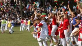 Children in Bright Costumes Dance Jump Wave Flags on Arena. KAZAN, TATARSTAN/RUSSIA - MAY 15 2013: Joyful children in bright costumes dance jump and wave small stock footage