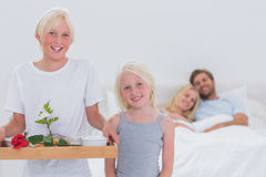 Children bringing breakfast in bed to their parents. Happy children bringing breakfast in bed to their parents Royalty Free Stock Image