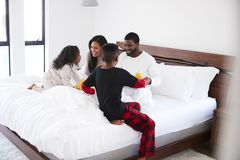 Children Bringing Parents Breakfast In Bed To Celebrate Mothers Day Fathers Day Or Birthday stock image