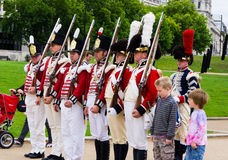 Children and British Royal Guard. Children and the British Royal Guard lined up Royalty Free Stock Photography