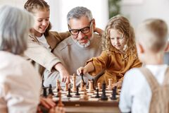 Children Brother And Sister Playing Chess While Sitting In Living Room With Senior Grandparents Royalty Free Stock Photography