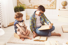 Children brother and sister, boy and girl reading a book Stock Photos
