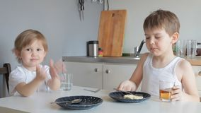Children brother and sister eat omelet, drink tea and water stock footage