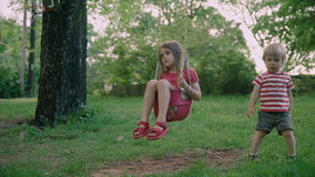 Children brother and sister in the park. Two little kids sitting in the park 4k. Children brother and sister in the park. Two little kids sitting in the park stock footage