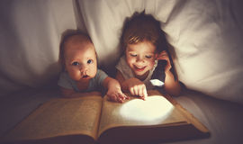 Children brother and sister read a book with aflashlight under b. Lanket in bed Stock Photo