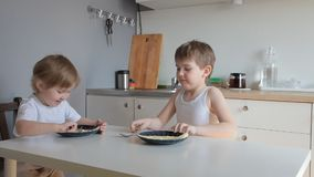 Children brother and sister sat at the table eat omelet stock video footage