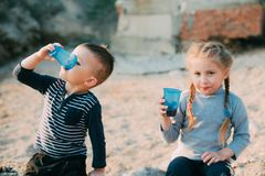 Children, brother and sister at sea drink from plastic blue cups of water or juice stock image