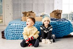 Children brother and sister sit on the floor in bedroom near the bed with gifts on the background of Christmas decor on a sunny da Royalty Free Stock Image