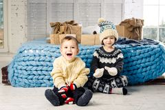 Children brother and sister sit on the floor in bedroom near the bed with gifts on the background of Christmas decor on a sunny da Stock Photos