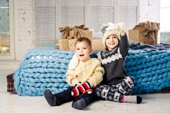 Children brother and sister sit on the floor in bedroom near the bed with gifts on the background of Christmas decor on a sunny da Royalty Free Stock Photography