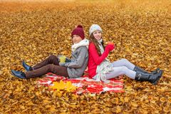 Children brother and sister are sitting with their backs to each other on a plaid in an autumn park and holding cups with hot tea. With fall leaves around Royalty Free Stock Images