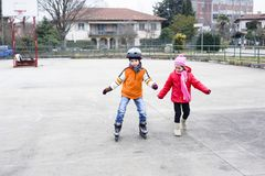 Children skate in the basketball field. Children, brother and sister, skate in the basketball field on a winter day Royalty Free Stock Photography