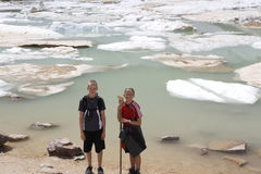 Children (brother and sister) stand in front of cavell lake with icebergs floating Royalty Free Stock Image