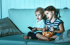 Children brother and sister watching TV in evening Royalty Free Stock Images