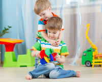 Children brothers play with educational toys indoors. Loving children brothers play with educational toys indoors Royalty Free Stock Photo