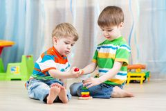 Children brothers play together in nursery. Children brothers playing together in nursery at home Royalty Free Stock Photos