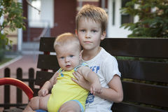 Children brothers sitting on bench Stock Photography