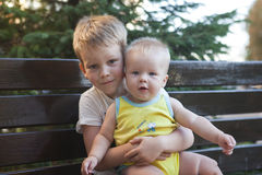 Children brothers sitting on bench Stock Photo