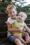 Children brothers sitting on bench Royalty Free Stock Photo
