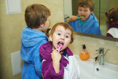 Children brush their teeth morning in the bathroom , dressed in robes Stock Image