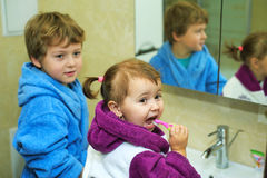 Children brush their teeth morning in the bathroom , dressed in robes Stock Photos