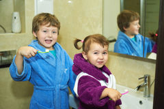 Children brush their teeth morning in the bathroom , dressed in robes Stock Images