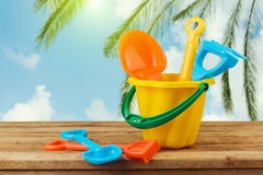 Children bucket and spade on wooden table over palm tree background royalty free stock images