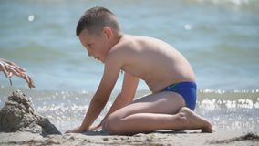 Children build a sand castle. On the beach stock video footage