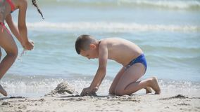 Children build a sand castle. On the beach stock footage