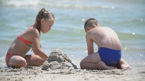 Children build a sand castle. On the beach stock video