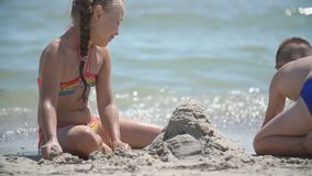 Children build a sand castle. On the seashore stock video footage