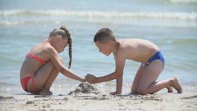 Children build a sand castle. On the seashore stock footage