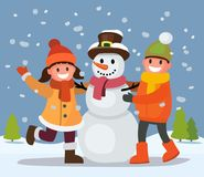 Children build snowman. Kids building snow man playing outdoors in winter day Royalty Free Stock Image