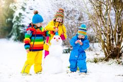 Kids building snowman. Children in snow. Winter fun. Stock Images