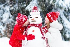 Kids building snowman. Children in snow. Winter fun. Children build snowman. Kids building snow men playing outdoors on sunny snowy winter day. Outdoor family Royalty Free Stock Photos