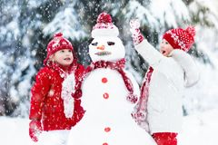 Kids building snowman. Children in snow. Winter fun. Children build snowman. Kids building snow men playing outdoors on sunny snowy winter day. Outdoor family Royalty Free Stock Image