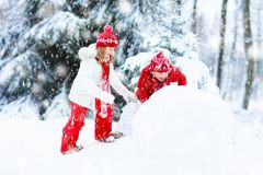 Kids building snowman. Children in snow. Winter fun. Stock Photography