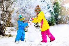 Kids building snowman. Children in snow. Winter fun. Children build snowman. Kids building snow men playing outdoors on sunny snowy winter day. Outdoor family Stock Photo