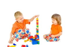 Children build a tower of the designer. A white background Royalty Free Stock Photo