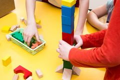 Children build tower of wooden blocks on the table Royalty Free Stock Photography