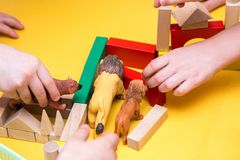 Children build tower of wooden blocks on the table Stock Image