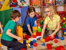 Children building blocks in kindergarten. Group kids playing toy floor. Stock Image