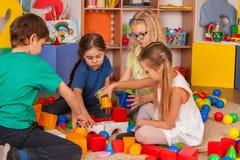 Children building blocks in kindergarten. Group kids playing toy floor. Royalty Free Stock Photo