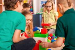 Children building blocks in kindergarten. Group kids playing toy floor. Children building blocks in kindergarten. Group kids playing toy on floor. Top view of stock photos