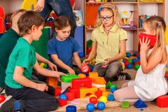 Children building blocks in kindergarten. Group kids playing toy floor. Royalty Free Stock Photography