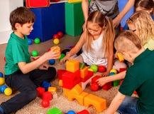 Children building blocks in kindergarten. Group kids playing toy floor. Royalty Free Stock Photography