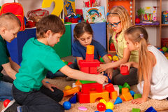 Children building blocks in kindergarten. Group kids playing toy floor. Children building blocks in kindergarten. Group kids playing toy on floor. Top view of royalty free stock images